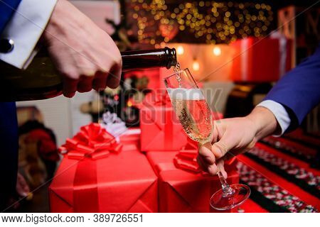 Cheers Concept. Hands Pouring Champagne Into Elegant Glass Christmas Decorations Background. Last Mi