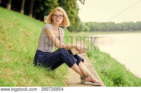 Rest Relax And Hobby. Vacation Season. Summer Vacation. Girl Sit On Green Grass Near River. Girl Rel