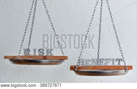 Words Risk And Benefit In Balance. Scales On White Background . Choice Concept.