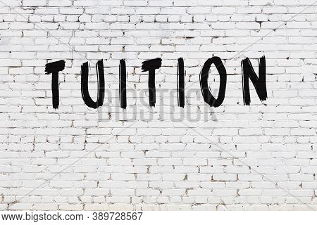 Inscription Tuition Written With Black Paint On White Brick Wall.
