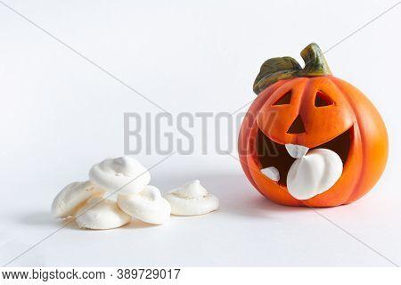 An Orange Cheerful Pumpkin Eats A Meringue Ghost, Next To A Handful Of Meringue On A White Backgroun
