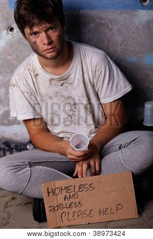 Dirty young homeless and jobless guy asking for help sitting on a street