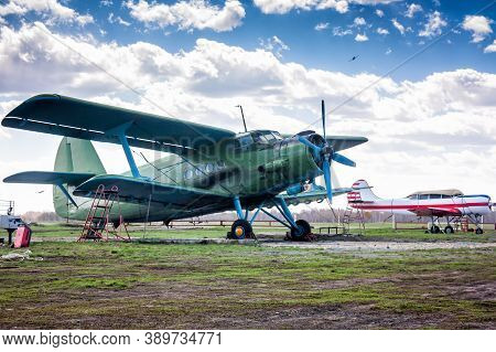Retro Passenger Biplane And Small Sports Airplane At The Ground Airfield