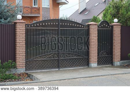 Black Metal Gates A Forged Pattern And Part Of A Brick Brown Fence On The Street