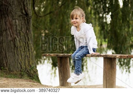 The Cute Little Girl Is Sitting On The Bench Outdoors.