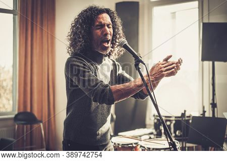 Artist Male Emotionally Sing Song Into Microphone .