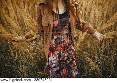 Stylish Boho Woman Walking Among Grass And Herbs In Autumn Field In Warm Sunset. Young Fashionable F