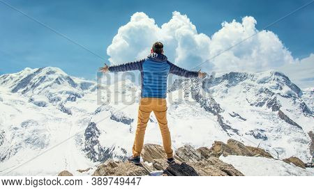 Zermatt, Switzerland - May 2017: Man At The Top Of Mountain Overlooking Snowy Mountain Landscape Wit