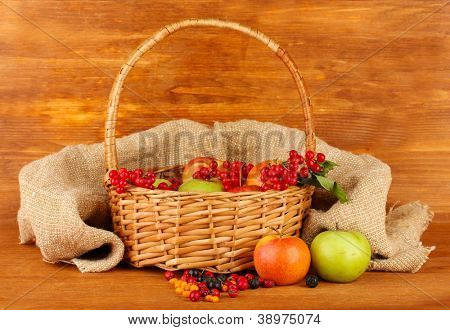 crop of berries and fruits in a basket on wooden background close-up