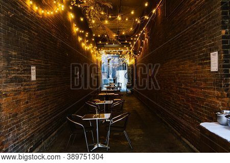 An Empty Outdoor Restaurant In Greenwich Village, Manhattan Set Up In Dark Corridor Because Covid Ou