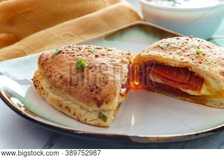 Italian Pastry Pepperoni And Cheese Calzone With Tomato Marinara Dipping Sauce