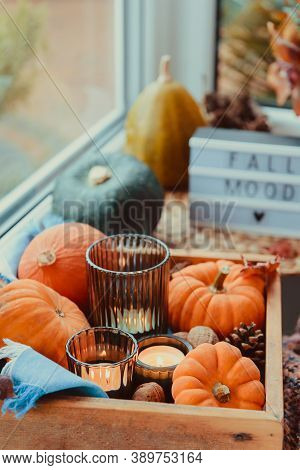 Autumn Cozy Mood Composition On The Windowsill. Pumpkins, Cones, Candles On Wooden Tray, Blurred Fal