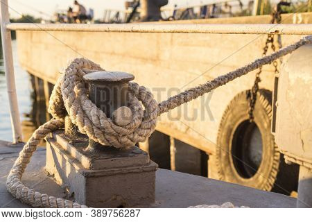 Tied Rope Knot On Metallic Bollard , Seafaring Port. Nautical Ship Moored In Dock. Anchor Rope In Th