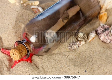 Glass bottle with note inside on sand