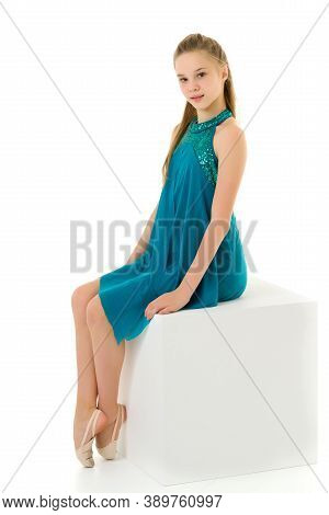 Elegant Little Gymnast Girl In A Beautiful Sports Swimsuit, On The Big White Cube In The Studio Perf