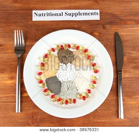 Nutritional supplements on wooden background close-up