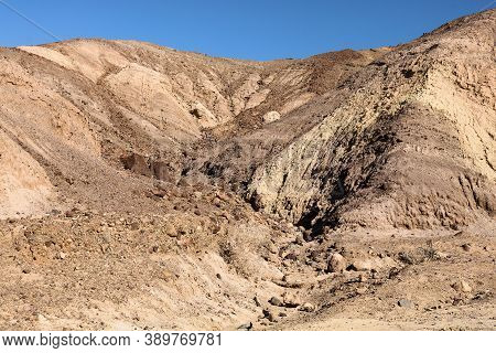 Barren Mountain Ridge With Eroded Rocks On A Drought Stricken Plain Taken At The Mojave Desert In De
