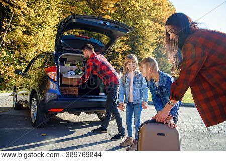 Joyful Lovely Young Family Loading The Autos Trunk By Carton Boxes And Suitcases While Relocating In
