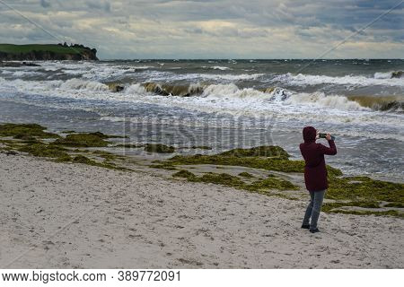 Woman Takes Photos Of Wild Waves In Storm And Onshore Wind At The Beach Of Boltenhagen At The Baltic
