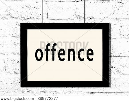Black Wooden Frame With Inscription Offence Hanging On White Brick Wall