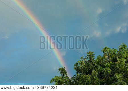 Natural Phenomenon Rainbow In Blue Sky With Cloud.