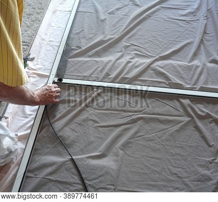 A Homeowner Is Preparing To Press In Spline In A Project To Replace A Damaged Mesh Panel In A Garage
