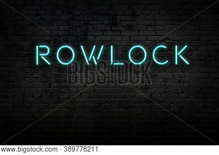 Neon Sign With Inscription Rowlock Against Brick Wall. Night View