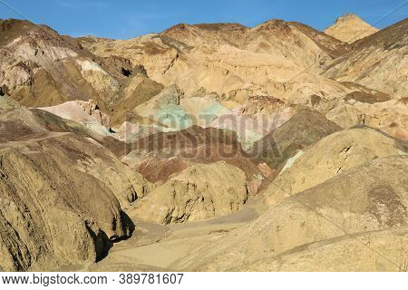 Barren Mountains With Eroded Colorful Rocks And Sand Taken At Arid Badlands In Death Valley National