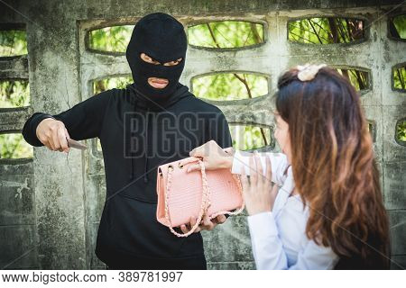The Robber Is Robbing The Female With A Knife, Pointing The Knife To The Face