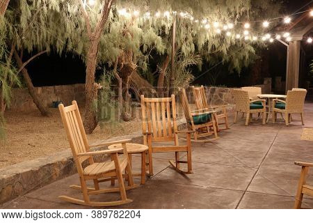 Contemporary Outdoor Patio Furniture Including Hanging Lamps Creating Lighting Above Wooden Rocking
