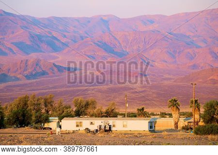Sunrise Over A Residential Neighborhood At The Town Of Furnace Creek, Ca With Barren Mountains Beyon