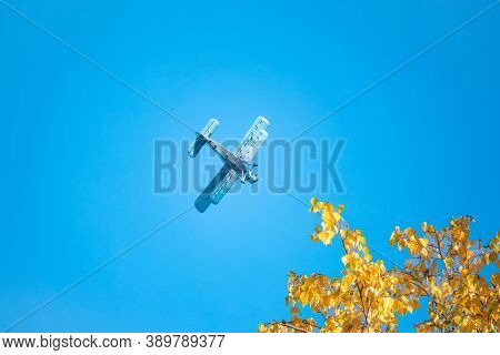 Retro Green Biplane Plane In The Blue Sky. Old Airplane Against Blue Sky. Autumn Yellow Leaves.