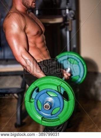 Sporty Man Lifts Barbell In Gym. Close Up Training With Barbell. Man Lifting Barbells Working Out In