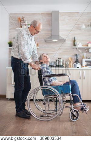 Husband Looking At Disabled Senior Woman In The Kitchen. Disabled Senior Woman Sitting In Wheelchair