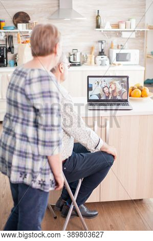Happy Senior Woman And Man Chatting With Family Via Internet Video Conference. Online Call With Daug