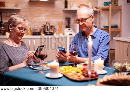Browsing On Smartphone In During Their Relationship Anniversary In Kitchen With Candles On Table. Si