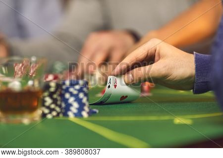 Closeup Of Gamblers Hand Holding A Pair Of Aces While Playing Poker On Casino Night