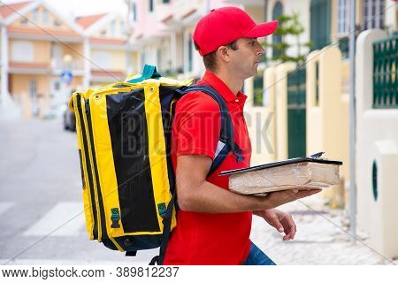 Caucasian Postman Holding Parcel And Delivering Order. Side View Of Deliveryman In Red Cap And Shirt