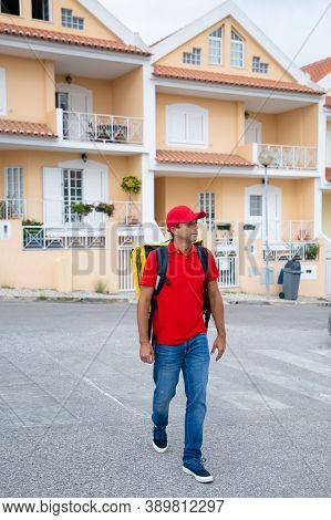 Confident Courier Delivering Order And Working In Post Service. Deliveryman Wearing Jeans, Red Cap A