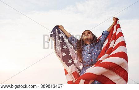 Patriotic Female Kid With American Flag In Hands. Against Cloudy Sky.
