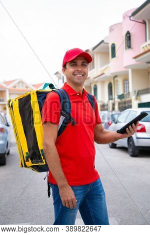 Happy Courier Delivering Order And Holding Tablet With Address. Smiling Caucasian Deliveryman Wearin