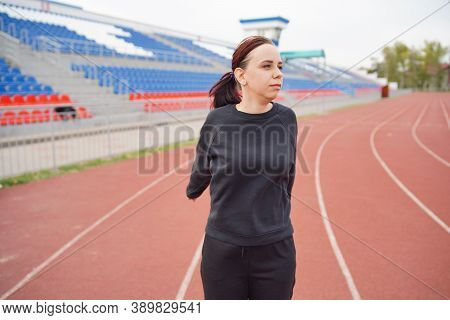 Young Woman In Medical Mask Doing Warm-up At Stadium. Adult Female In Black Casual Clothes Doing Spo