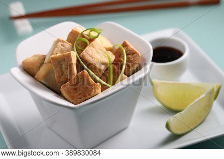 Fried tofu served with soy sauce, slices of lime, and green onion on a white plate closeup
