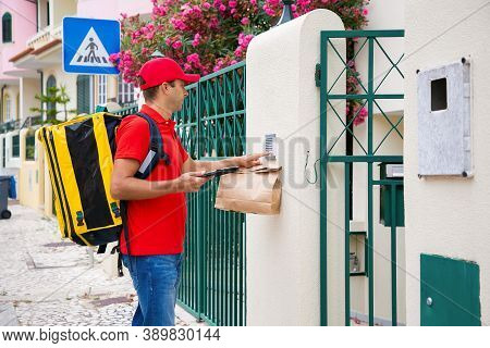 Pensive Deliveryman In Red Cap Ringing In Doorbell Of Recipient. Middle-aged Courier With Yellow The