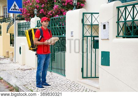 Pensive Postman Standing On Pavement And Holding Parcel. Caucasian Middle-aged Courier Waiting For C
