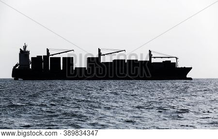 Container Ship Goes On Sea. Blue Toned Silhouette Photo
