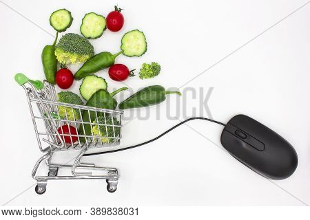 Mini Shopping Cart Or Trolley Full Of Vegetables Next To A Computer Mouse On White Background. Healt