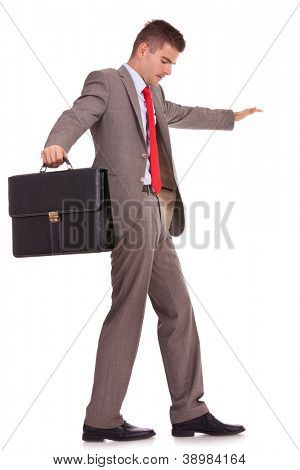 side view of a young business man holding a briefcase balancing and walking forward on an imaginary rope
