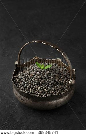 Heap Of Black Gram Or Urad Beans Or Mung Beans With Green Leaf On Top In Iron Basket On Dark Slate T