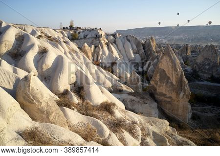 Valley With Volcanic Tuff Stone Rocks In Goreme, Turkey. Hot Air Balloons Flying Over Rocky Formatio